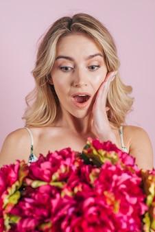 Geschokte blonde jonge vrouw die bloemboeket bekijkt
