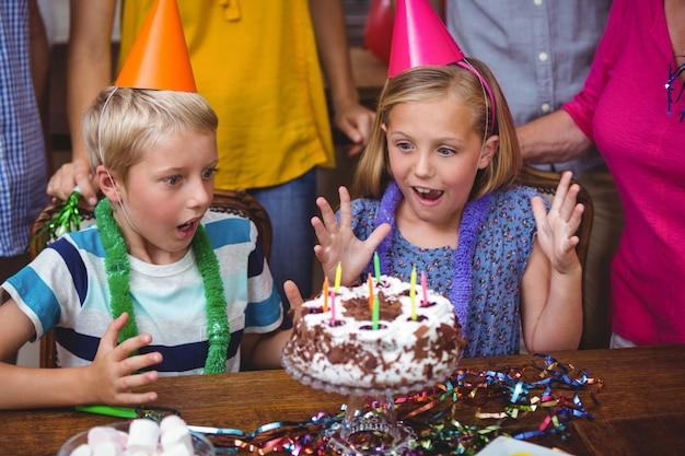 Geschokte broers en zussen met verjaardagstaart
