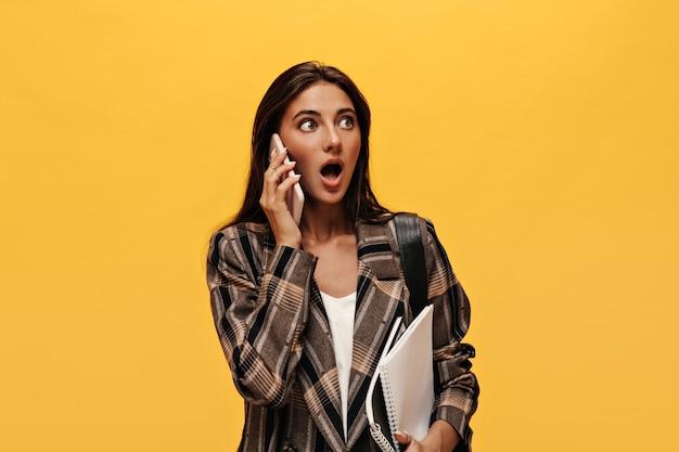 Geschokte brunette vrouw in witte top en stijlvol jasje praat aan de telefoon en houdt notitieboekjes vast op geïsoleerde gele muur