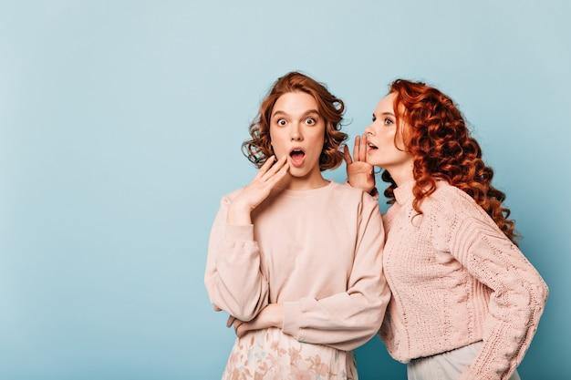 Geschokte dames die geruchten delen. studio shot van verbaasde roddelmeisjes die zich voordeed op blauwe achtergrond.