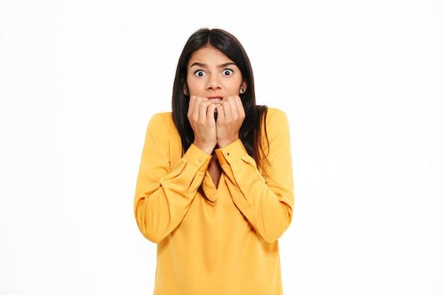 Geschokte doen schrikken jonge dame in gele overhemd geïsoleerde status