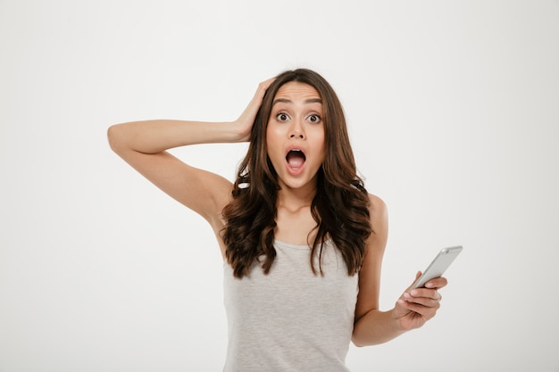 Geschokte donkerbruine vrouw met het hoofd van de smartphoneholding en het bekijken de camera over grijs