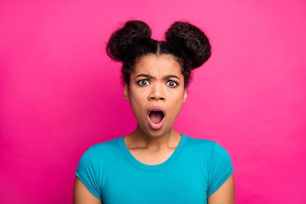 Geschokte donkere huiddame die de blauwe uitdrukking van het t-shirt met open mondgezicht op roze achtergrond draagt