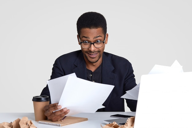 Geschokte donkere man draagt veel papieren, kijkt verrassend door een bril, draagt formele kleding en een bril, zit op dektop, geïsoleerd op wit. mensen en werkconcept