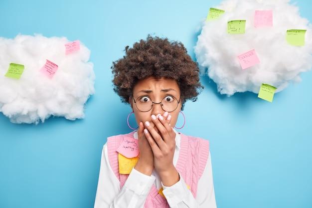 Geschokte doodsbange afro-amerikaanse student kijkt met omg-uitdrukking bedekt mond realiseert examen morgen niet goed voorbereid heeft deadline draagt ronde bril