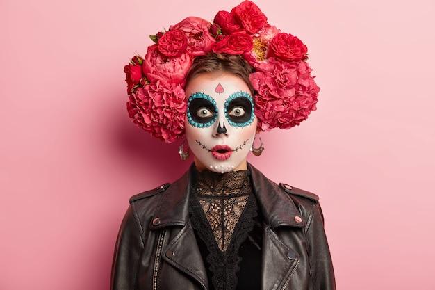 Geschokte, doodsbange jonge vrouw heeft een eng spookgezicht, draagt artistieke make-up voor day of dead-vakantie, draagt een zwart leren jack, modellen op een roze studioachtergrond. schedel vrouwtje symboliseert de dood
