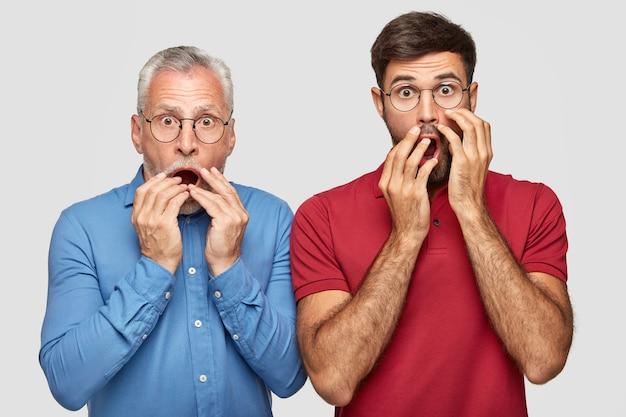 Geschokte emotionele vader en zoon kijken met angstige uitdrukkingen, houden de handen bij de mond