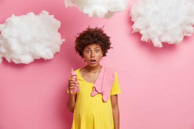 Geschokte emotionele zwangere vrouw gekleed in een gele jurk, heeft een ronde buik, poseert met babyartikelen, realiseert zich dat er nog twee weken voor de bevalling zijn, bijna negen maanden van opwindende verwachtingen achter.