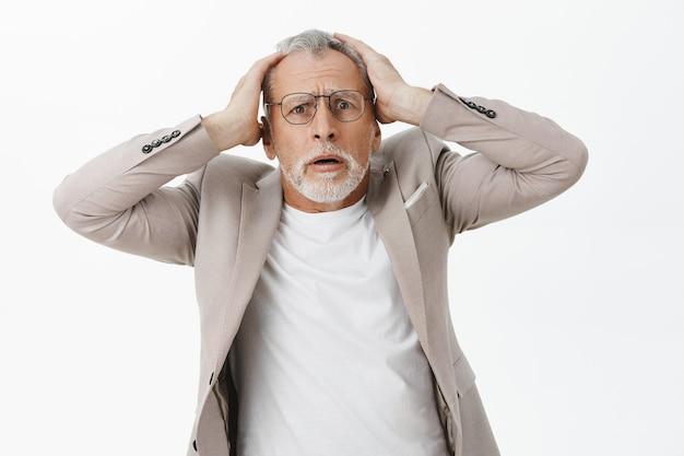 Geschokte en bezorgde oudere man grijpt zijn hoofd en kijkt angstig