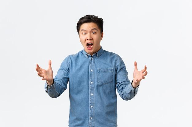Geschokte en gealarmeerde aziatische man die reageert op verschrikkelijk nieuws, in paniek over een witte achtergrond staat en handen besluiteloos schudt, weet niet wat doen, nutteloos gevoel, witte achtergrond.