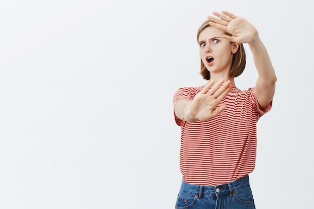 Geschokte en gekke jonge vrouw die verdedigend handen opheft en zichzelf beschermt