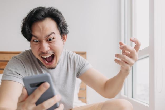 Geschokte en gelukkige man krijgt goed nieuws van de smartphone