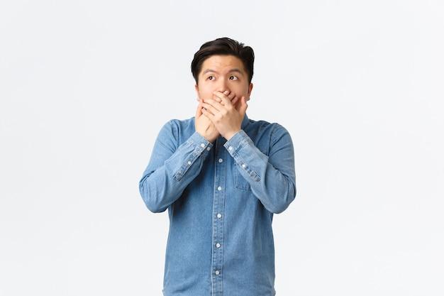 Geschokte en sprakeloze aziatische man is getuige van iets, bedek de mond met handen en kijkt naar de linkerbovenhoek, hijgend verbaasd van openbaring, hoor verbluffende roddels, witte achtergrond.