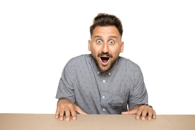 Geschokte en verbaasde man die het grootste postpakket opent. opgewonden jong mannelijk model bovenop een kartonnen doos die naar binnen kijkt.