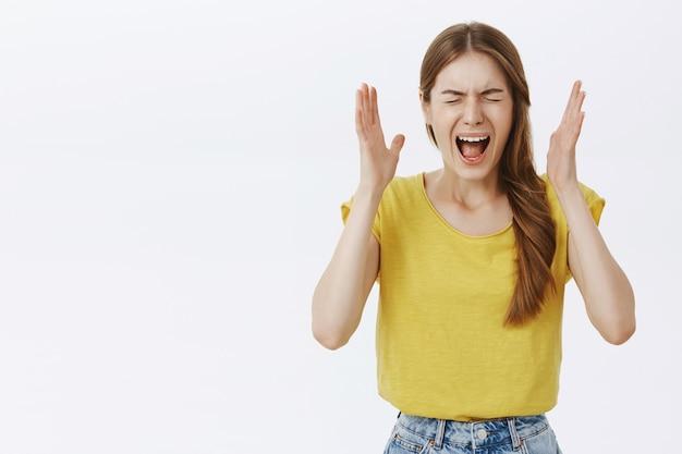 Geschokte en verontruste jonge vrouw die gefrustreerd en bezorgd kijkt, in paniek raakt en schreeuwt