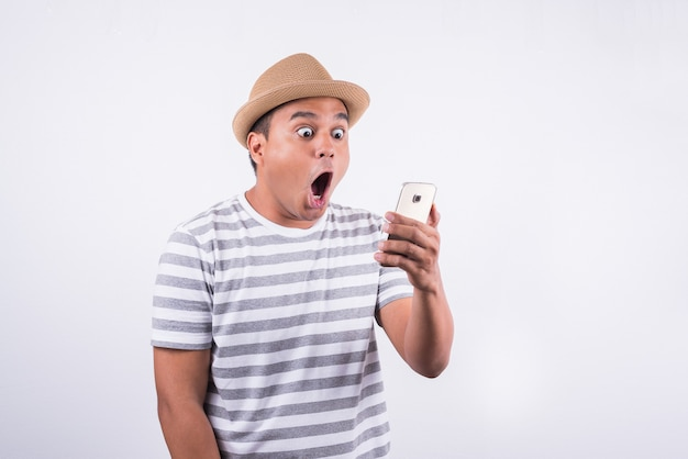 Geschokte en verraste aziatische mens die smartphone kijken