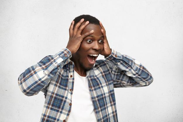 Geschokte en versuft jonge afro-amerikaanse man in geruit hemd die zijn hoofd vasthoudt met beide handen voor zich uit kijkend met open ogen en wijd opengesperde mond, kan zijn geluk, overwinning of succes niet geloven