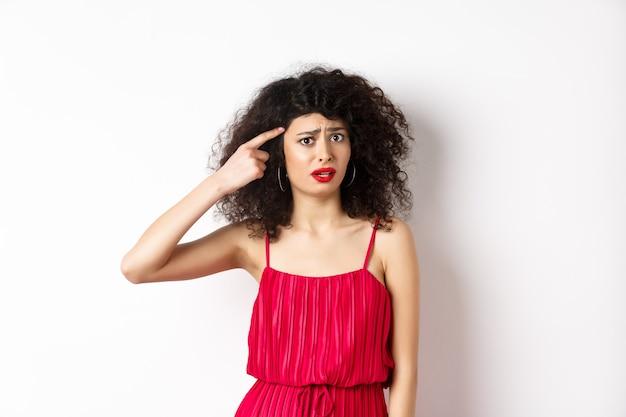 Geschokte en verwarde blanke vrouw in rode jurk die gek iemand uitscheldt, met de vinger naar het hoofd wijst en fronst, staande op een witte achtergrond.