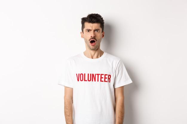 Geschokte en verwarde man in vrijwilligerst-shirt die naar de camera staart en ontevreden fronst, staande tegen een witte achtergrond