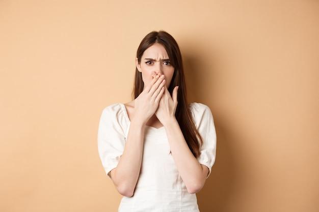 Geschokte en verwarde vrouw fronsend van streek over haar mond met handen teleurgesteld over iets vreselijks...