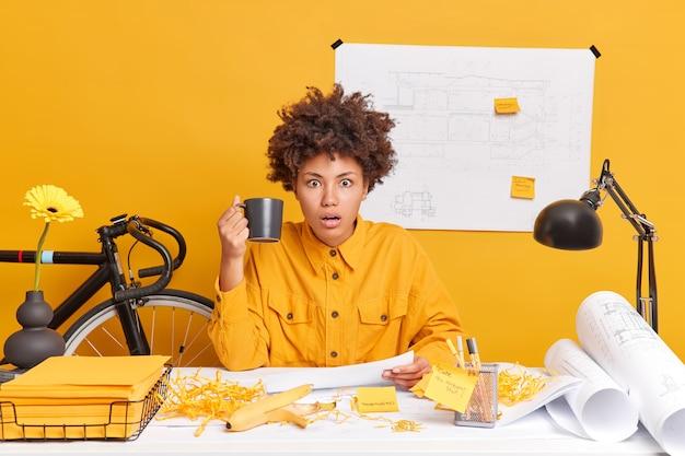 Geschokte etnische vrouwelijke architect werkt aan gedetailleerde bouwblauwdrukken heeft koffiepauze poses bij dekstop staart onder de indruk, bereidt project voor draagt geel shirt houdt kopje drank vast