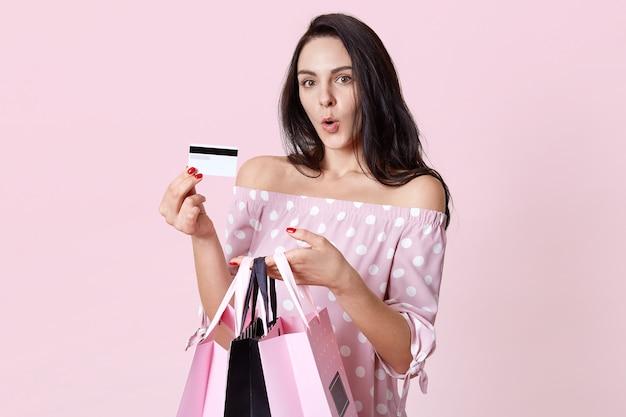 Geschokte europese vrouw houdt tassen vast, houdt haar lippen rond, verbaasd om onbeperkte plastic kaart te ontvangen, gekleed in een jurk met stippen, wil iets anders kopen, poseert tegen roze muur