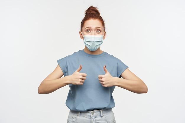 Geschokte, gelukkig ogende vrouw met roodbruin haar in een knot. blauw t-shirt en beschermend gezichtsmasker dragen. duimen opdagen van opwinding. geïsoleerd over witte muur