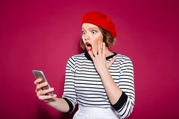 Geschokte gembervrouw die wang houden terwijl het gebruiken van smartphone over roze