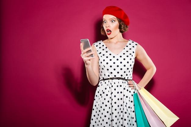 Geschokte gembervrouw in kleding met pakketten die smartphone over roze gebruiken