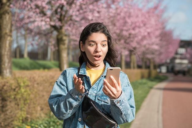 Geschokte gezichtsuitdrukking van een vrouw van gemengd ras die in de telefoon kijkt terwijl ze in de bloeiende lente op straat loopt.