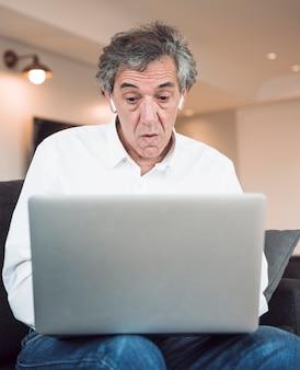Geschokte hogere mens die laptop bekijkt