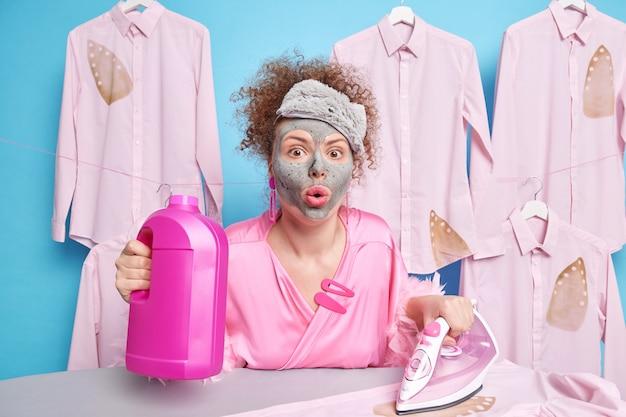 Geschokte huisvrouw met krullend haar ziet er verwonderd uit, gekleed in casual huishoudelijke kleding, past een kleimasker toe met een fles wasmiddel en een elektrisch strijkijzer bezig met wassen en strijken.