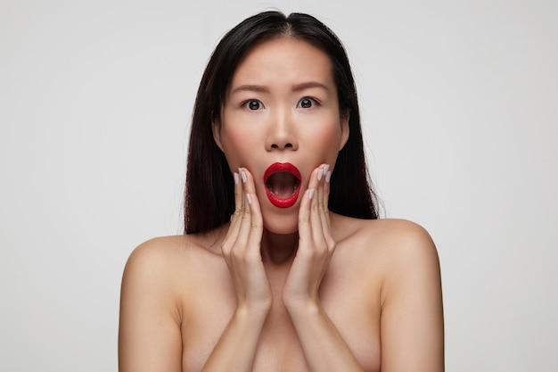 Geschokte jonge aantrekkelijke donkerharige vrouw met feestelijke make-up die handpalmen op haar gezicht houdt en verbaasd kijkt met geopende mond, geïsoleerd over witte muur
