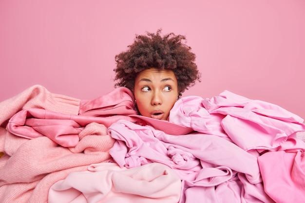 Geschokte jonge afro-amerikaanse vrouw toont alleen hoofd begraven in grote hoop kleren kijkt weg met verbijsterde uitdrukking verzamelt kleding voor donatie geïsoleerd over roze