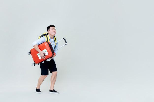 Geschokte jonge aziatische mensentoerist die met bagage stijgend kijken
