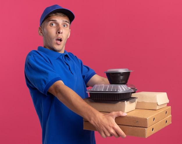 Geschokte jonge blonde bezorger houdt voedselcontainers en -pakketten op pizzadozen geïsoleerd op roze muur met kopieerruimte