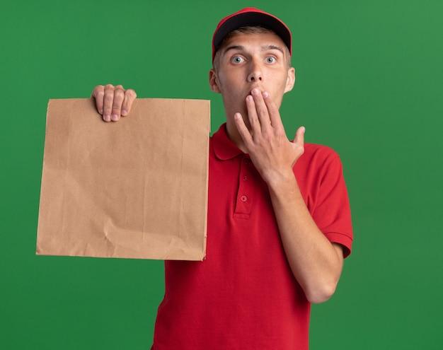 Geschokte jonge blonde bezorger legt hand op mond en houdt papieren pakket vast