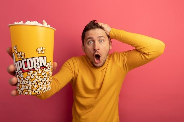 Geschokte jonge blonde knappe man die een emmer popcorn uitrekt en hand op het hoofd zet