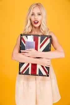 Geschokte jonge blonde vrouw die britse gedrukte koffer houdt