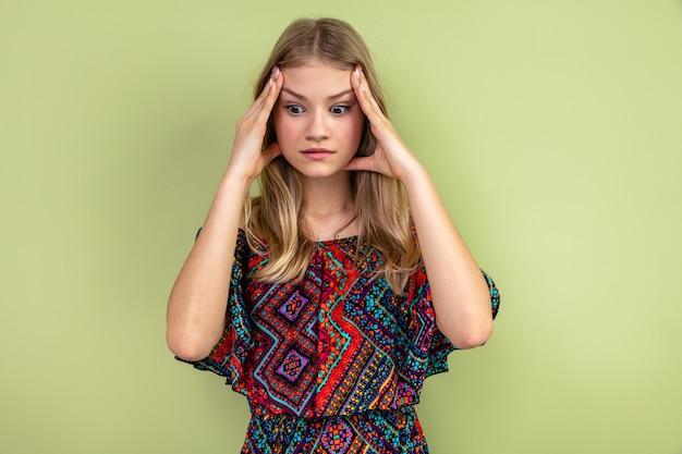 Geschokte jonge blonde vrouw die haar hoofd vasthoudt en naar de zijkant kijkt