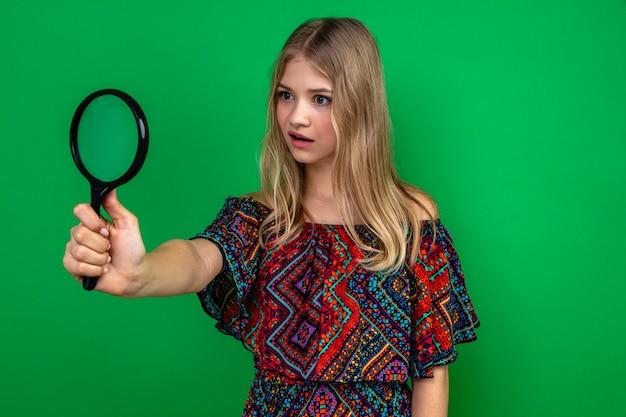 Geschokte jonge blonde vrouw die vergrootglas vasthoudt en bekijkt