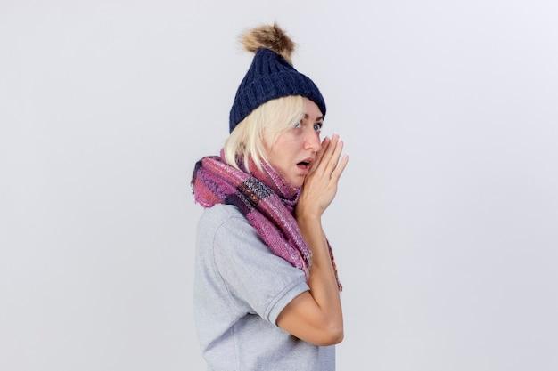 Geschokte jonge blonde zieke vrouw die de wintermuts en sjaal draagt, staat zijwaarts met de hand dicht bij de mond geïsoleerd op een witte muur