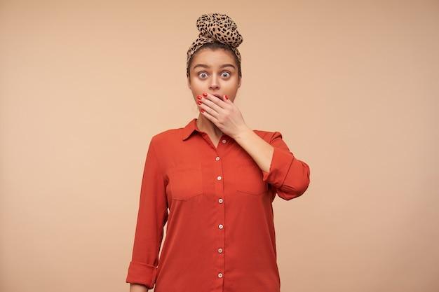 Geschokte jonge bruinharige vrouw die haar mond bedekt met opgeheven handpalm terwijl ze verbaasd naar de voorkant kijkt met grote ogen geopend, geïsoleerd over beige muur