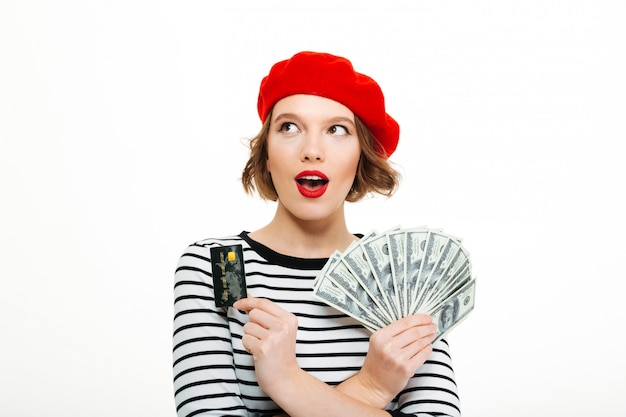 Geschokte jonge dame die gelddollars en creditcard houdt