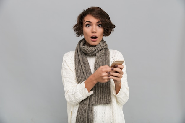 Geschokte jonge dame die sjaal draagt die door mobiele telefoon babbelt.