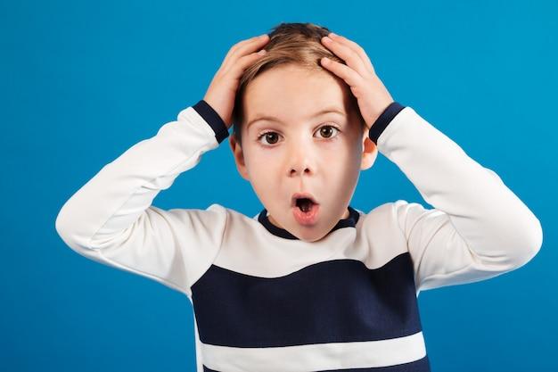 Geschokte jonge jongen in het hoofd van de sweaterholding
