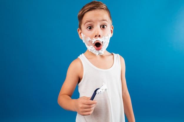 Geschokte jonge jongen in scheerschuim zoals het scheermes van de mensenholding