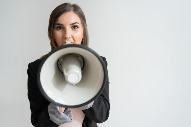 Geschokte jonge kaukasische vrouw die bij u in megafoon schreeuwt