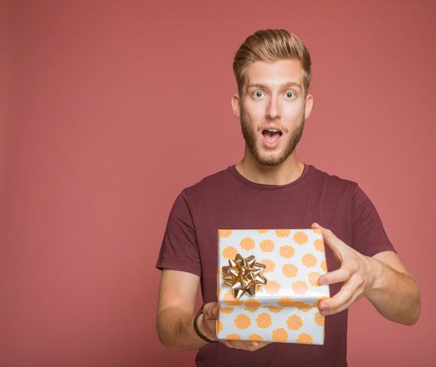 Geschokte jonge man die een bloemengiftdoos opent met gouden boog