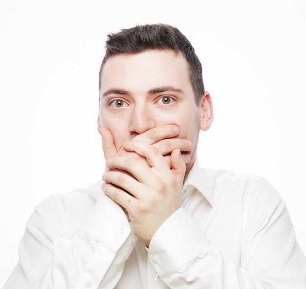 Geschokte jonge man die mond behandelt met handen